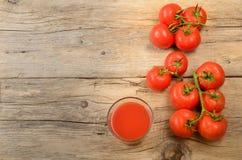 Tomates y jugo recién cosechados y mojados en un rústico, de madera foto de archivo libre de regalías