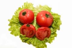 Tomates y lechuga frescos en un fondo blanco Imagen de archivo
