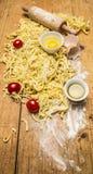 Tomates y pastas crudos con la harina, los huevos y cierre rústico de madera de la opinión superior del fondo de la sal para arri Imágenes de archivo libres de regalías