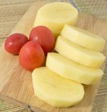 Tomates y patatas frescos en el tablero de madera Imagen de archivo