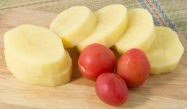 Tomates y patatas frescos en un tablero de madera Foto de archivo libre de regalías