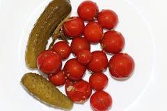 Tomates y pepinos adobados en el lugar blanco fotos de archivo libres de regalías