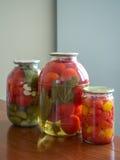 Tomates y pepinos conservados en los tarros de cristal Imagenes de archivo