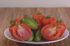 Tomates y pepinos en una placa Imagenes de archivo