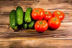 Tomates y pepinos frescos en la tabla de madera Fotografía de archivo