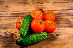 Tomates y pepinos maduros en la tabla de madera Foto de archivo
