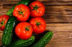 Tomates y pepinos maduros en la tabla de madera Visión superior Fotografía de archivo libre de regalías