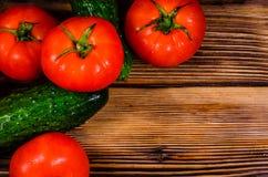 Tomates y pepinos maduros en la tabla de madera Visión superior Imagen de archivo