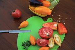 Tomates y pimientas cortados en la tabla del ¾ n de la tabla de cortar Ð Cierre para arriba Foto de archivo libre de regalías