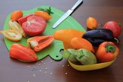Tomates y pimientas cortados en la tabla del ¾ n de la tabla de cortar Ð Cierre para arriba Fotos de archivo libres de regalías
