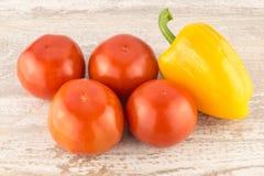 Tomates y pimientas dulces del amarillo en un cierre de madera blanco del fondo para arriba Imágenes de archivo libres de regalías
