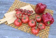 Tomates y pimientas en un fondo de madera y una estera de la paja Imagen de archivo