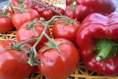 Tomates y pimientas en un fondo de madera y una estera de la paja Foto de archivo