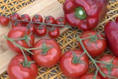 Tomates y pimientas en un fondo de madera y una estera de la paja Fotos de archivo libres de regalías