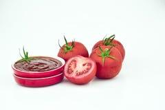 Tomates y una taza de salsa Foto de archivo libre de regalías
