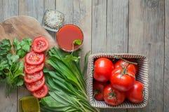 Tomatesap, een grote tak van rijpe rode tomaten op een houten Raad met bladeren van ramsonanddille in een rustieke stijl Stock Foto's