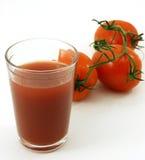 Tomatesap en tomaten op de wijnstok Royalty-vrije Stock Foto