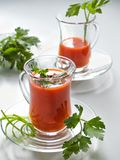 Tomatesap in glasmokken op glasplaten Stock Fotografie