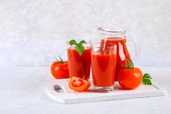 Tomatesap in glazen en een waterkruik op een grijze concrete lijst Royalty-vrije Stock Foto