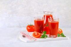 Tomatesap in glazen en een waterkruik op een grijze concrete lijst Royalty-vrije Stock Afbeeldingen