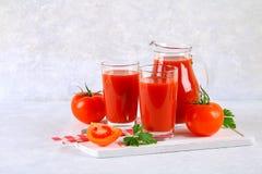Tomatesap in glazen en een waterkruik op een grijze concrete lijst Stock Afbeeldingen