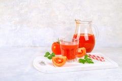Tomatesap in glazen en een waterkruik op een grijze concrete lijst Stock Foto's