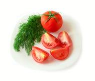 Tomatescheiben und -dill auf einer Platte. Getrennt. Stockfoto