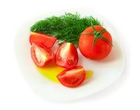 Tomatescheiben und -dill auf einer Platte mit Olivenöl Lizenzfreie Stockbilder