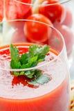 Tomatfruktsaft i ett exponeringsglas med en kvist av ny persilja på en bakgrund av körsbärsröda tomater i ett exponeringsglas Arkivfoton