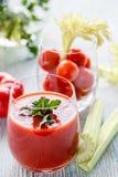 Tomatfruktsaft i ett exponeringsglas med persilja, körsbärsröda tomater i ett exponeringsglas med selleri på en trätabell Royaltyfri Bild