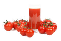 Tomatfruktsaft och massor av tomater över vit Arkivbilder