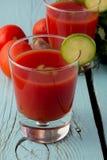 Tomatgazpacho i exponeringsglas över den blåa trätabellen Fotografering för Bildbyråer