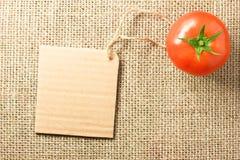 Tomatgrönsak och prislapp på att plundra bakgrundstextur Royaltyfri Bild