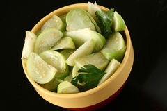 Tomatillo slices in bowl with cilantro. Freshly cut tomatillo slices in bowl with cilantro and black background Royalty Free Stock Photos