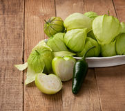 Tomatillos and Jalapeno in Rustic Setting. Many Tomatillos in a white dish with one sliced in half and a jalapeno all in a rustic setting of used boards royalty free stock images