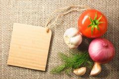 Tomatlök och vitlökgrönsaker och prislapp på plundra baksida Fotografering för Bildbyråer