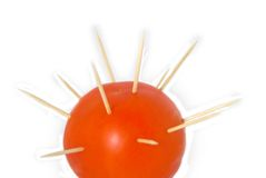 Tomato. With the needles thrust in it on a white background Royalty Free Stock Photography
