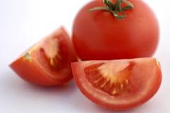 Tomato. Whole and quartered tomato on white endless background Stock Image