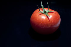 Tomato. Single with drops isolated on black stock images