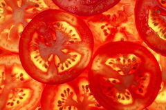 Tomato. Bright red background of the pieces of tomato Stock Image