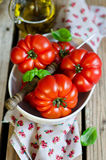 Tomato. Fresh tomatoes in a cup with a basil Royalty Free Stock Photo