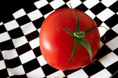 Tomato. Fresh tomato on a chess plate Stock Photo