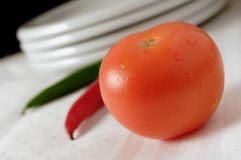 Tomato. And some chilis in background stock photo
