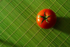 Tomato. Fresh tomato an a green bamboo rug Royalty Free Stock Photos