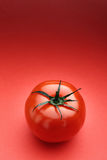Tomato. A single tomato with leaves on a red background Stock Photos