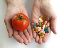 Free Tomato And Handfull Of Pills Royalty Free Stock Photography - 24470147
