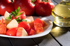 Tomato and apples in a bowl on a dark table. Bottle with oil. Vegan diet. Stock Photos