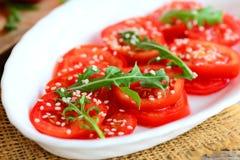 Tomato and arugula salad recipe. Home fresh tomatoes, arugula and sesame seeds salad on a white plate Stock Photos