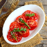 Tomato, arugula and sesame seeds salad with home vinaigrette dressing. Simple tomato salad on a white plate and burlap textile Stock Photography