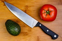 A Tomato and an Avocado on a cutting board with a Chef`s knife royalty free stock photos